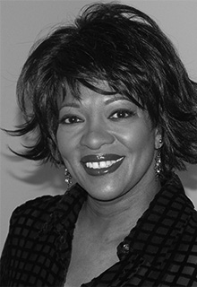 A black and white image of a black woman smiling