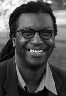 A black and white image of a black man smiling