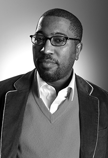 A black and white image of a black man wearing glasses