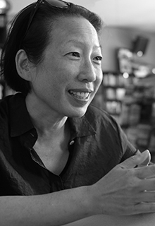 A black and white image of an asian woman smiling