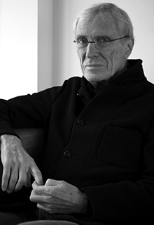 A black and white image of a white man wearing glasses and a black shirt