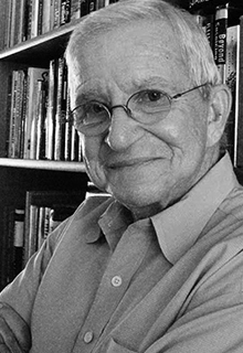 A black and white image of a white man smiling in front of a stack of books